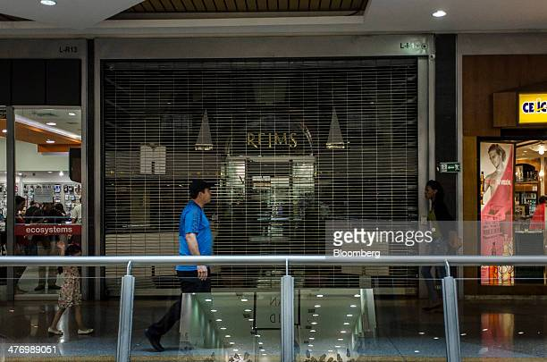 Shoppers pass by a shuttered store in the Sambil shopping center in the Chacao section of Caracas Venezuela on Friday Feb 28 2014 Antigovernment...