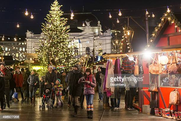 Shoppers pass festive stalls as a Christmas tree stands illuminated at a Christmas market in front of the opera house in Zurich Switzerland on...