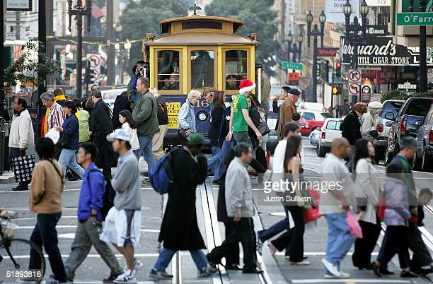 Shoppers pass in front of a cable car as they walk through the Union Square shopping district December 24, 2004 in San Francisco, California....