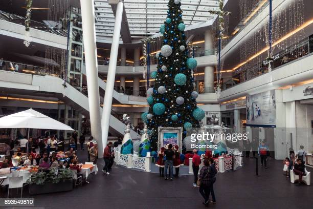 Shoppers pass in front of a Christmas tree displayed at the Plaza Reforma 222 mall in Mexico City Mexico on Monday Nov 20 2017 The National Institute...