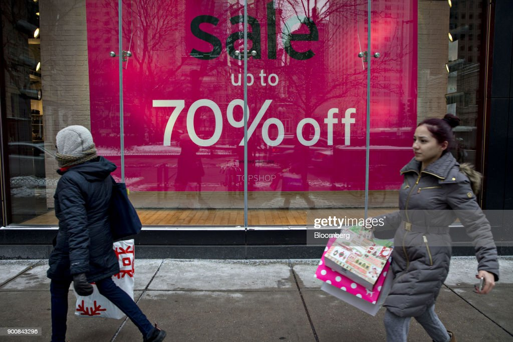 Shoppers pass in front of a 'Sale' sign displayed in the window a Top Shop Ltd. store at the Magnificent Mile commercial district in Chicago, Illinois, U.S., on Friday, Dec. 29, 2017. Bloomberg is scheduled to release consumer comfort figures on January 4. Photographer: Daniel Acker/Bloomberg via Getty Images