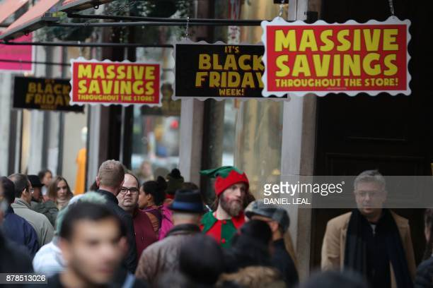 Shoppers pass promotional signs for 'Black Friday' sales discounts on Oxford Street in London on November 24 2017 Black Friday is a sales offer...