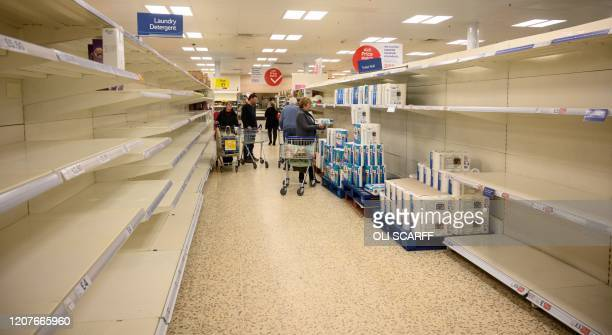 Shoppers peruse nearempty toilet roll shelves at a supermarket in the centre of York northern England on March 19 2020 Britain's supermarkets on...