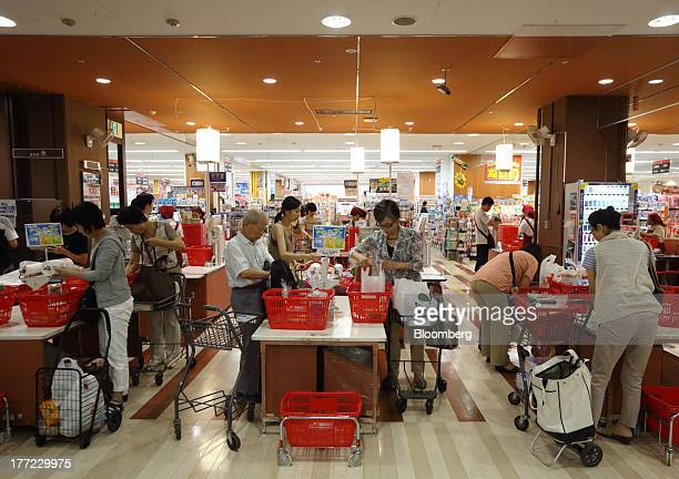 Shoppers put their purchased goods into shopping bags at a Daiei Inc supermarket during a sale jointly held with Aeon Co at a Daiei supermarket in...