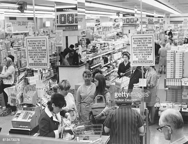 Shoppers queue at the cash tills in a Tesco's supermarket where notices inform customers about changes resulting from the move towards decimalization