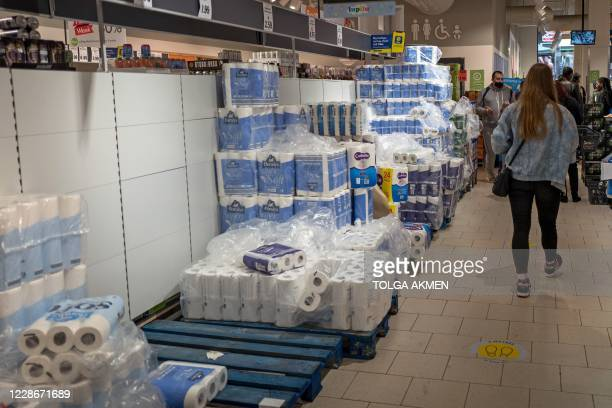 Shoppers queue for self-checkout tills next to aisle of toilet paper at Lidl supermarket in Walthamstow, east London on September 23, 2020. - Britain...