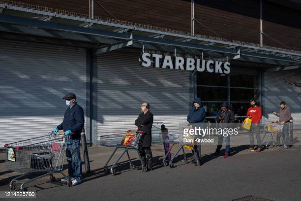 Shoppers queue outside a Sainsbury's supermarket ahead of opening on March 23 2020 in London England Coronavirus pandemic has spread to at least 182...