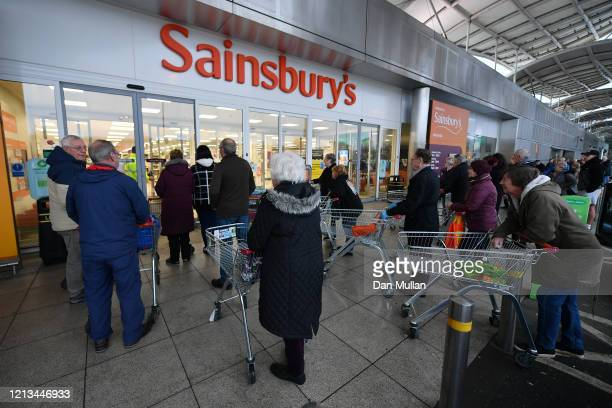 Shoppers queue outside a Sainsbury's supermarket prior to opening in Plymouth on March 19, 2020 in Plymouth, United Kingdom. The store allowed only...
