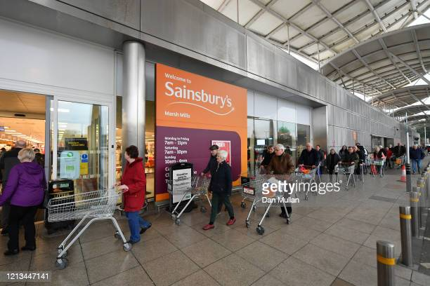 Shoppers queue outside a Sainsbury's supermarket prior to opening in Plymouth on March 19 2020 in Plymouth United Kingdom The store allowed only the...