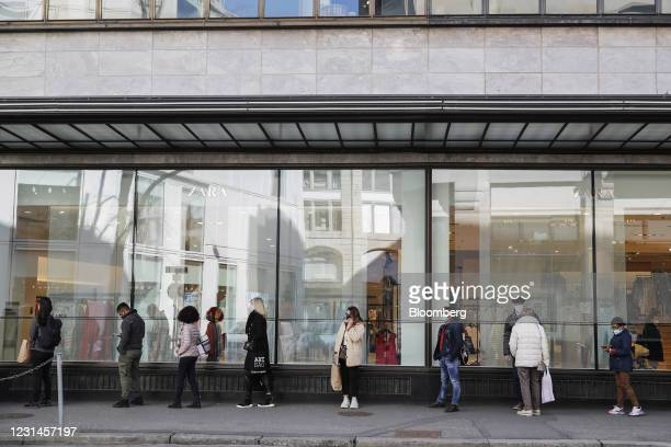 Shoppers queue outside a Zara clothing store, operated by Inditex SA, in Zurich, Switzerland, on Monday, March 1, 2021. Switzerland has allowed...