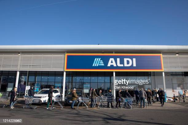 Shoppers queue outside an Aldi supermarket on March 23, 2020 in London, England. Coronavirus pandemic has spread to at least 182 countries, claiming...