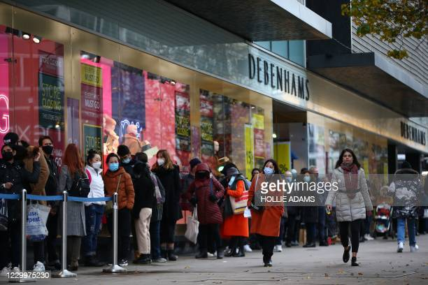 Shoppers queue outside Debenhams on Oxford Street in London on December 6, 2020. - Shoppers returned to Englands high streets this week as shops...