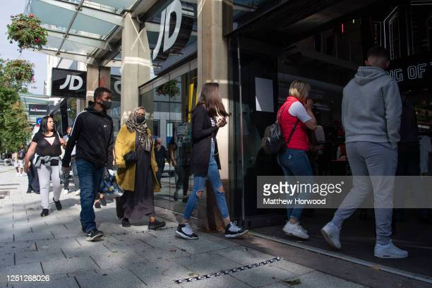 Shoppers queue outside JD sports as non-essential shops open for the first time since the start of lockdown on June 22, 2020 in Cardiff, United...