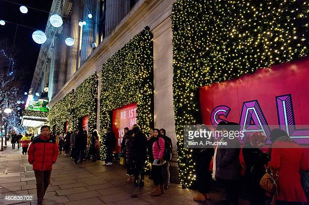 Shoppers queue outside Selfridges ahead of the annual boxing day sales at Selfridges on December 26 2014 in London England