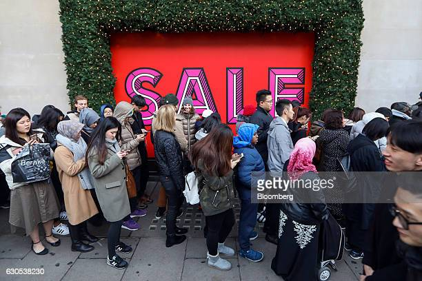 Shoppers queue outside Selfridges Plc department store ahead of the Boxing Day sales in London UK on Monday Dec 26 2016 Consumer confidence fell to...