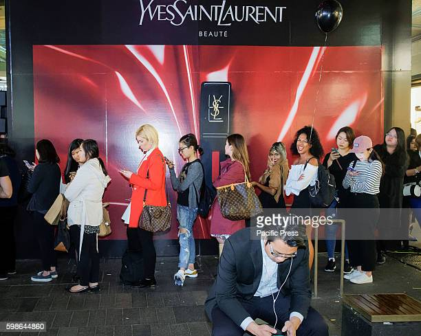 Shoppers queue outside the Yves Saint Laurent Popup display in Sydney's Pitt Street Mall during the Vogue American Express Fashions Night Out in...