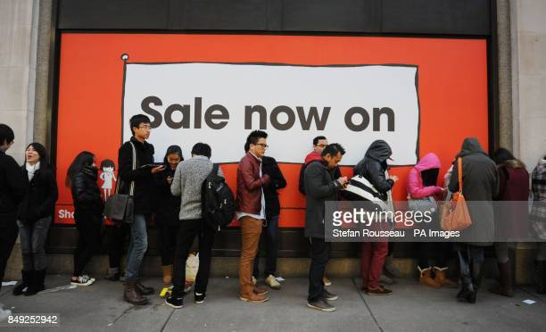 Shoppers queue to enter Selfridges department store in London's Oxford Street where they took Acircpound15 million in the first hour of trading of...