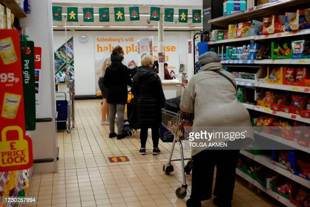 Shoppers queue to pay for their goods at a check-out desk inside a Sainsbury's supermarket in Walthamstow in north east London on December 22, 2020....