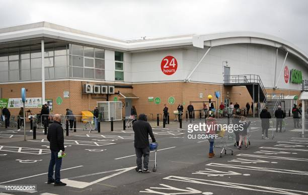 Shoppers queue using social distancing outside an Asda supermarket in Gateshead northeast England on April 9 2020 as Britain continued to battle the...