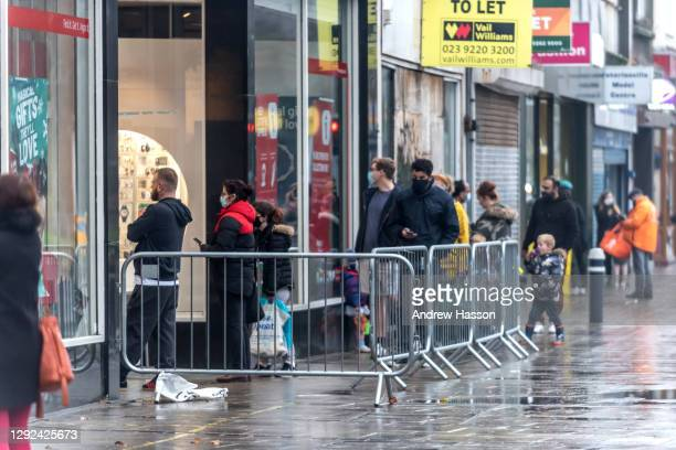 Shoppers queueing outside Argos on Commercial Road on December 21, 2020 in Portsmouth, United Kingdom. A new strain of the Covid-19 virus has led to...