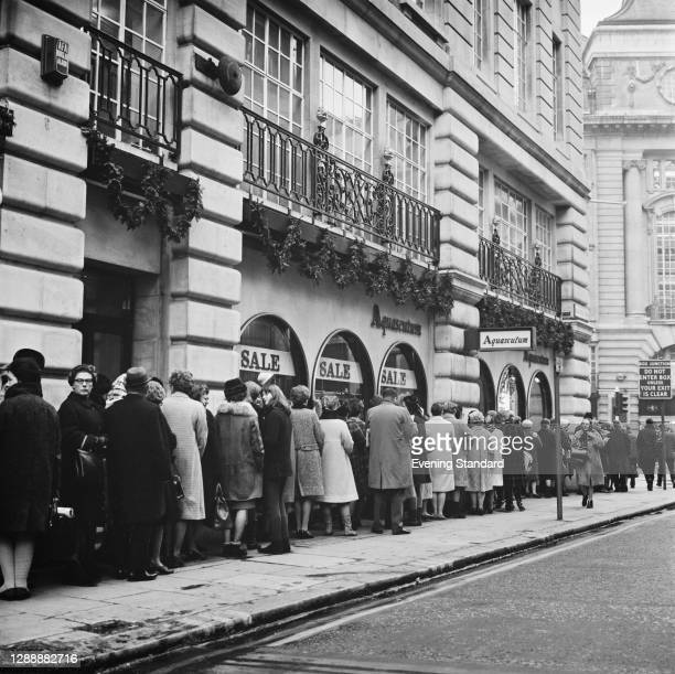 Shoppers queuing outside Aquascutum in Regent Street, London, during a winter sale, UK, January 1968.