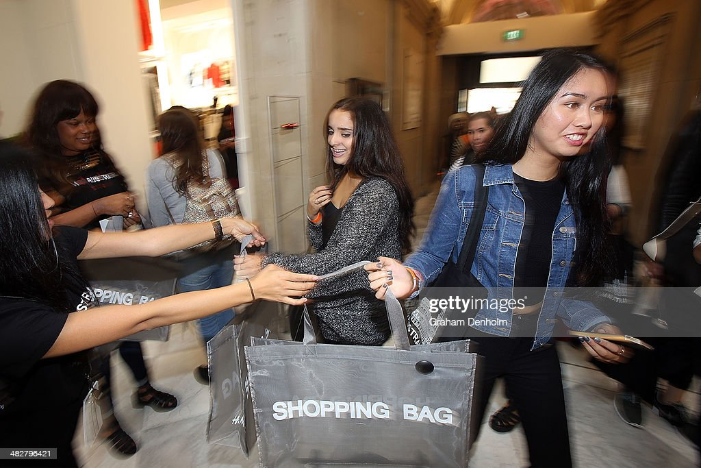 Shoppers receive shopping bags from staff members as they enter the store at the opening of the first H&M Australia store at the GPO on April 5, 2014 in Melbourne, Australia.