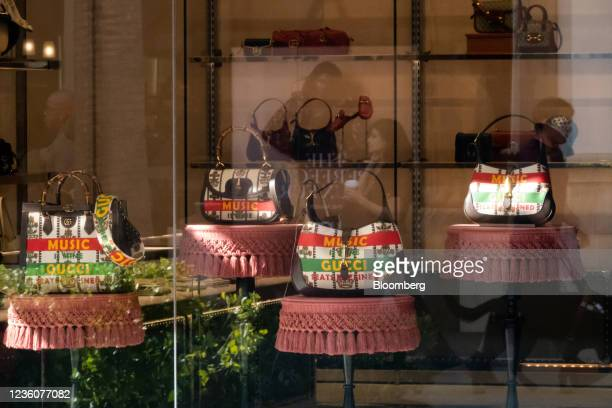 Shoppers reflected in the windows of a Gucci luxury clothing store at the Fashion Valley shopping mall in San Diego, California, U.S., on Friday,...