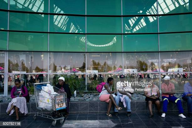 Shoppers relax outside a mall on May 1 2013 at Maponya shopping Mall Soweto South Africa Maponya is one of several new shopping malls in the township...