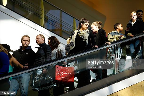 Shoppers ride an escalator as they shop for Black Friday deals at Somerset Collection shopping mall on November 29 2013 in Troy Michigan Black Friday...