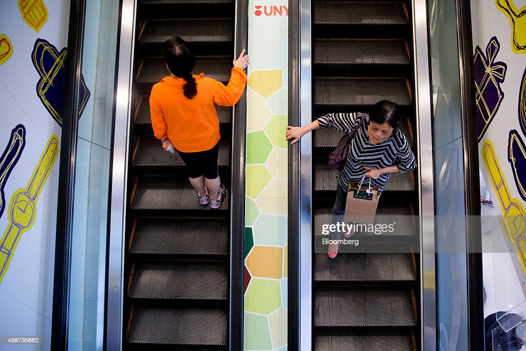 Shoppers ride an escalator at Lok Fu Plaza, operated by the Link Real Estate Investment Trust (REIT), in Hong Kong, China, on Monday, Nov. 10, 2014. The Link REIT, Asia's largest property trust which owns neighborhood malls, food markets, and car parks, is scheduled to announce interim results on Nov. 13. Photographer: Brent Lewin/Bloomberg via Getty Images