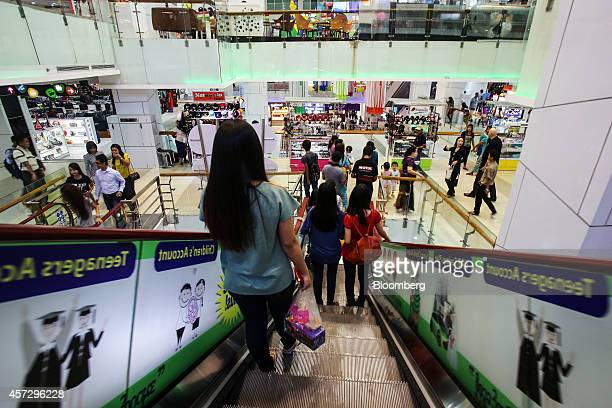 Shoppers ride an escalator at the Junction Square shopping mall operated by the Junction Center Group in Yangon Myanmar on Tuesday Oct 14 2014...