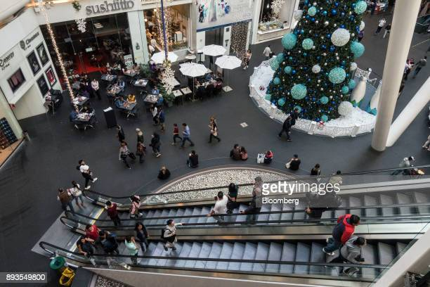 Shoppers ride an escalator in front of a Christmas tree at the Plaza Reforma 222 mall in Mexico City Mexico on Monday Nov 20 2017 The National...