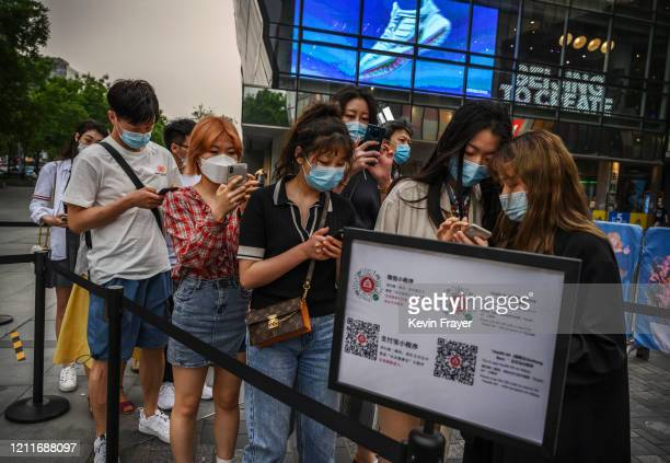 Shoppers scan their local health QR codes from the Beijing Municipality to show security before entering a shopping area during the May holiday on...