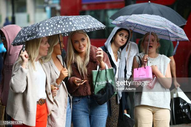 Shoppers shelter from the rain as they wait to cross Oxford Street on July 31, 2021 in London, England. The United Kingdom, considered one of the...