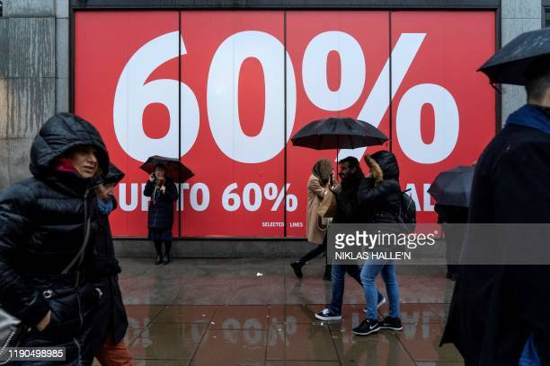 Shoppers shelter under umbrellas as they hunt for bargains during the Boxing Day sales in central London on December 26, 2019. - With environmental...