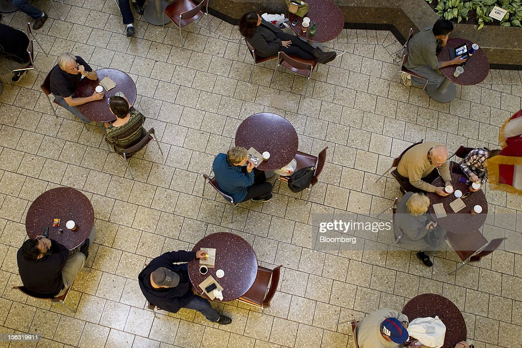 Shoppers sit at at tables while taking a break next to a Starbucks Corp. store inside the Fair Oaks Mall in Fairfax, Virginia, U.S., on Monday, Nov. 12. 2012. Sales at U.S. retailers probably fell in October for the first time in four months economists said before a report on Nov. 14. Photographer: Andrew Harrer/Bloomberg via Getty Images