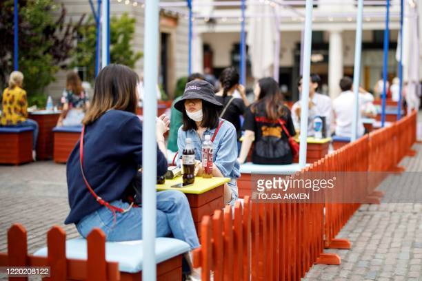 Shoppers sit at socially distanced tables as they eat take-away food outside of Covent Garden in London on June 15, 2020 as some non-essential...