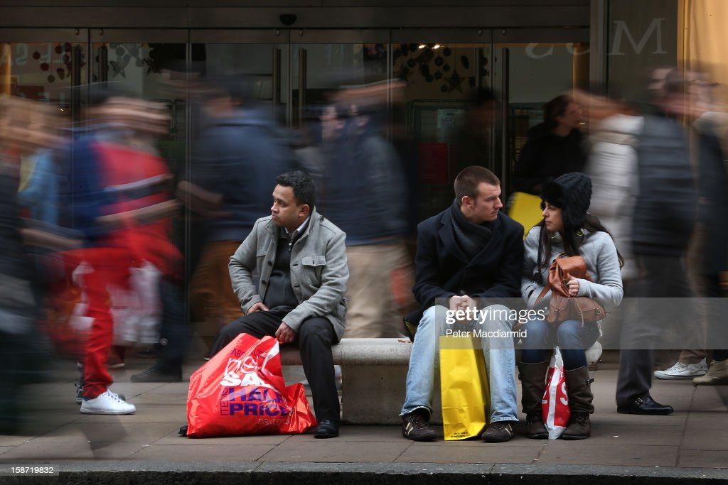 Shoppers sit on benches in a busy Oxford Street on December 26, 2012 in London, England. Thousands of shoppers are in London looking for a bargain in the traditional Boxing Day sales.