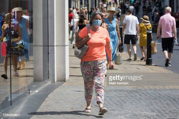 Shoppers, some of whom wearing face coverings, are pictured on 'Freedom Day', when the UK government lifted almost all remaining Covid-19...