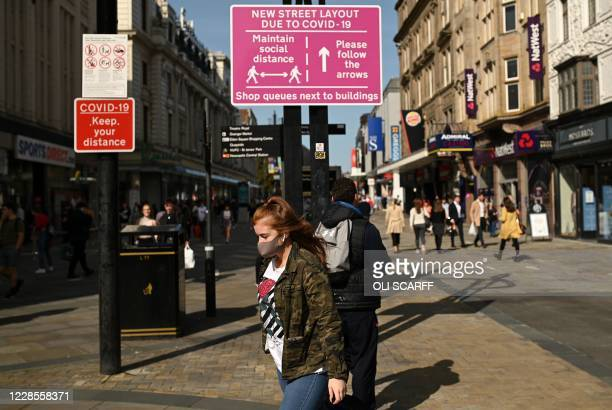 Shoppers, some wearing a face mask or covering due to the COVID-19 pandemic, walk past a sign alerting pedestrians to a one-way system to assist with...