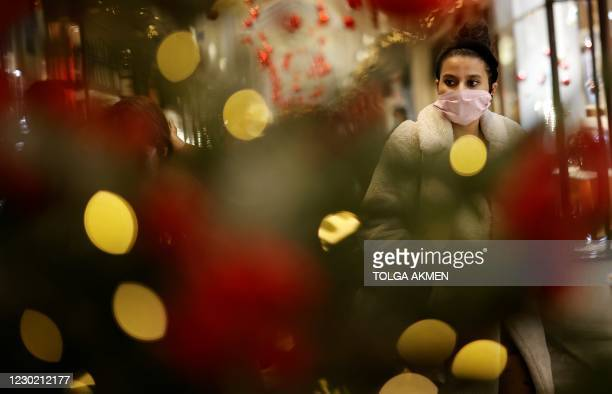 Shoppers, some wearing a face mask or covering due to the COVID-19 pandemic, look at shop window displays inside a christmas-themed Burlington Arcade...