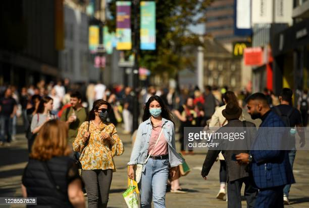 Shoppers, some wearing a face mask or covering due to the COVID-19 pandemic, walk in Newcastle city centre, north-east England, on September 17,...