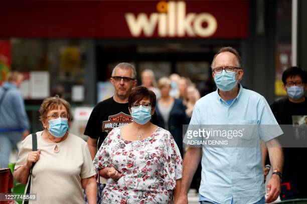 Shoppers some wearing a face mask or covering due to the COVID19 pandemic walk past shops in Basingstoke south west of London on July 23 as consumers...