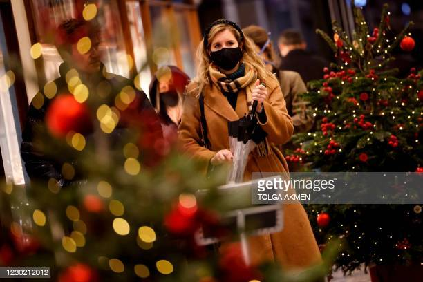 Shoppers, some wearing a face mask or covering due to the COVID-19 pandemic, walk through the christmas-themed Burlington Arcade shopping centre in...
