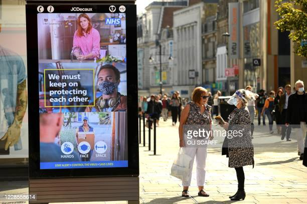 Shoppers, some wearing a face mask or covering, walk past an electronic billboard displaying a UK Government advert advising the public to take...