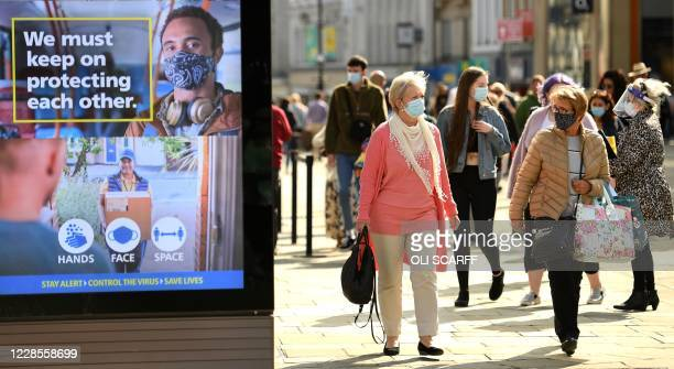 Shoppers some wearing a face mask or covering walk past an electronic billboard displaying a UK Government advert advising the public to take...