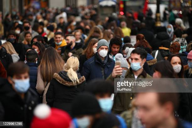 Shoppers, some wearing face masks, walk along a busy Oxford Street in London, England, on December 5, 2020. London has returned to so-called Tier 2...