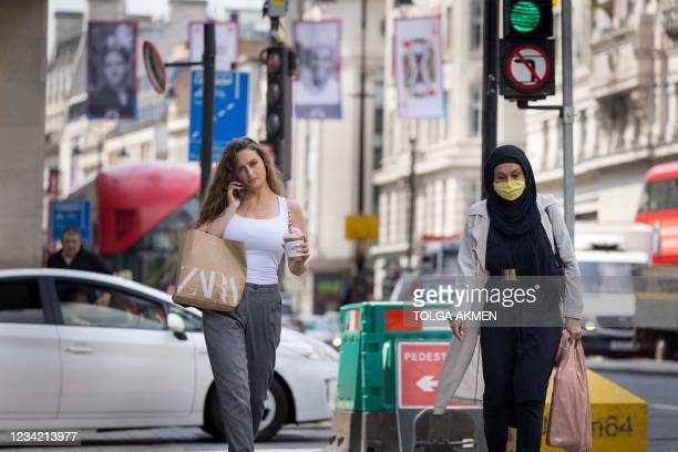 Shoppers, some wearing face masks, walk along The Strand in central London on July 26, 2021. - For the first time in the latest wave of coronavirus...