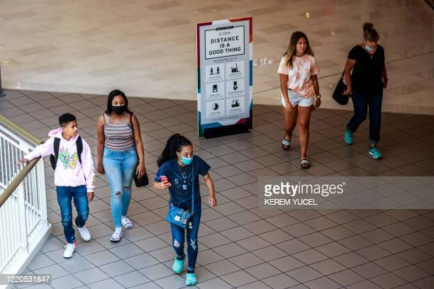Shoppers, some wearing facemasks, walk at the Mall of America on June 16, 2020 in Bloomington, Minnesota, after some of the shops at the mall...