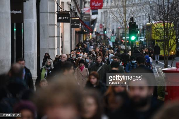 Shoppers, some wearing masks because of the coronavirus pandemic, walk along Regent Street in the main high-street shopping area of London on...